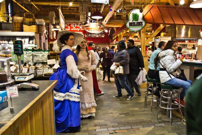 Amanda Daly and Elizabeth Cascarelli greet Reading Terminal Market shoppers at the 125th anniversary celebration. (Kimberly Paynter/WHYY)