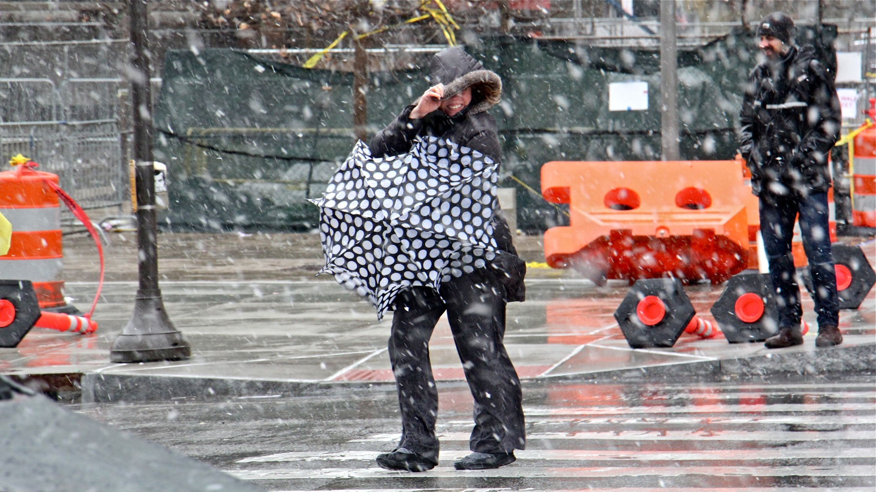 A pedestrian in Center City struggles against the strong winds and pelting snow.