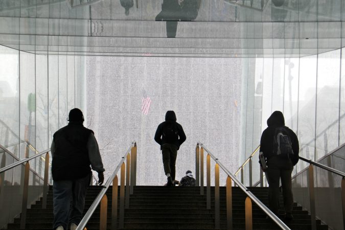 Travelers emerge from the Dilworth Park subway station into a wintry world. (Emma Lee/WHYY)