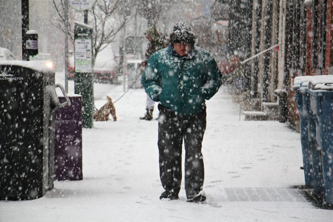 Pedestrians in Old City are coated in snow. (Emma Lee/WHYY)