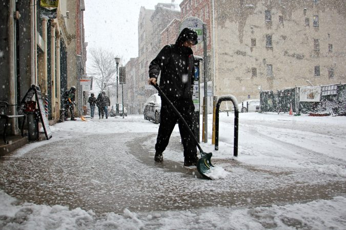 Shovelers clear snow in front of businesses on Third Street in Old City. (Emma Lee/WHYY)