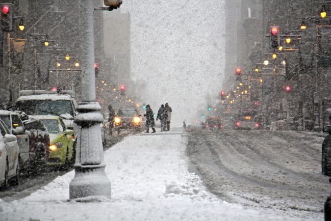Snow falls fast and thick on South Broad Street near City Hall. (Emma Lee/WHYY)