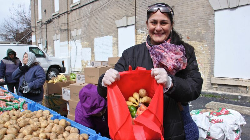 Philabundance volunteer Charito Morales shows off a bag full of fresh produce at the free farmers market at Lillian Marerro Library. (Emma Lee/WHYY)