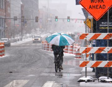 A bicyclist makes his way west on Market Street, protected from the heavy wet snow of the latest nor'easter by an oversized umbrella. (Emma Lee/WHYY)