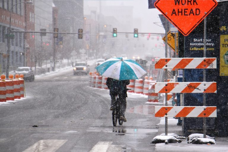 A bicyclist makes his way west on Market Street, protected from the heavy wet snow by an oversized umbrella. (Emma Lee/WHYY)