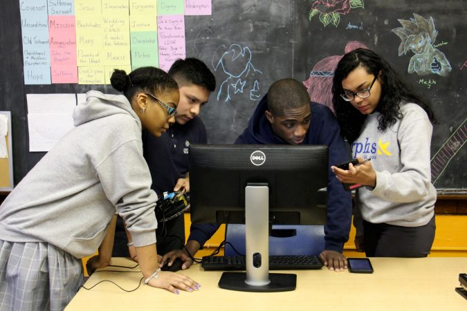 Cristo Rey students (from left) Catherine Santille, Ramiro Ortega-Zavaleta, Kemar Marshall and Maria Tejada Caceres  troubleshoot the programming for their team vehicle. (Emma Lee/WHYY)