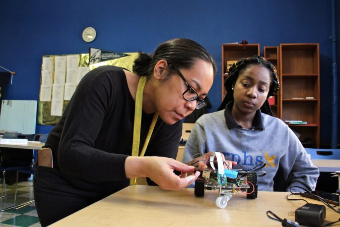 Engineering teacher Eva Porter helps Neriah Garrett with her prograammable vehicle. (Emma Lee/WHYY)