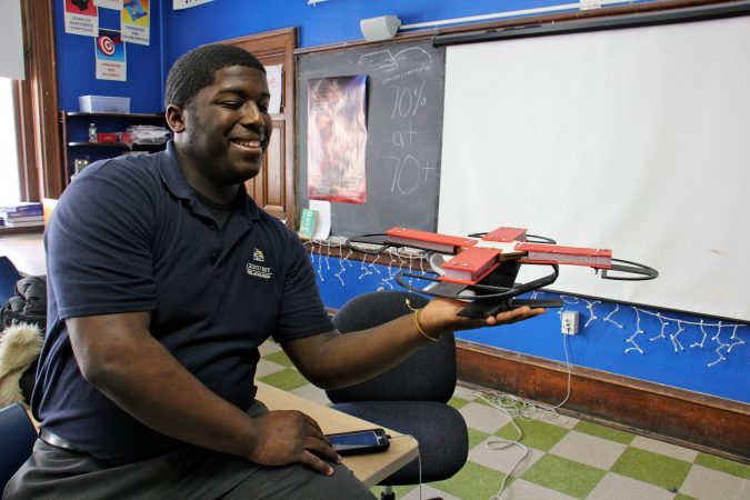 Cristo Rey student Kevin Riddick holds the drone frame he constructed during the first trimester of his autonomous systems engineering class. At the end of the third semester, he and his team will program and test fly the drone. (Emma Lee/WHYY)