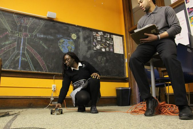 Cristo Rey student Monica Kpedenou demonstrates her program for monitor Jared Boyd during a timed test. (Emma Lee/WHYY)