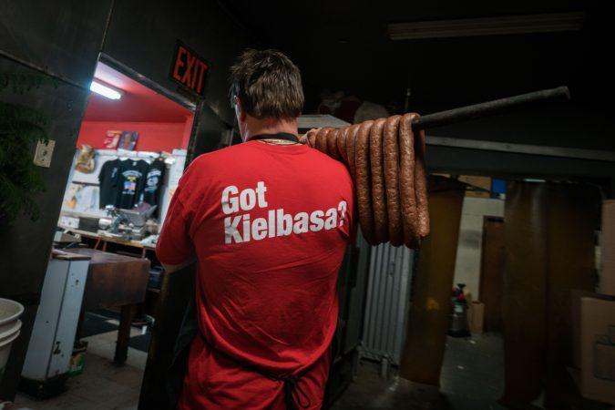 John Czerw carries Kielbasa to waiting customers at Czerw's Polish Kielbasa in Port Richmond. (Branden Eastwood for WHYY)