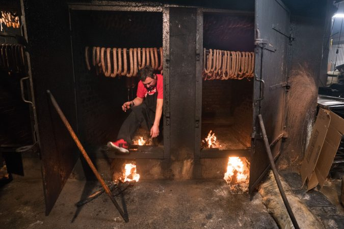 John Czerw steps out of the smokehouse at Czerw's Polish Kielbasa in Port Richmond. (Branden Eastwood for WHYY)