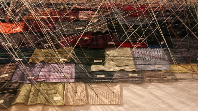 Donated sweaters are connected by threads in Jean Shin's