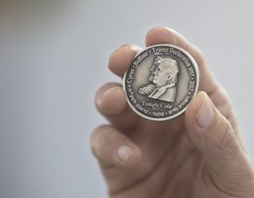 Head of the Mikdash Educational Center, Rabbi Mordecahi Persoss, holds a coin they minted bearing President Donald Trump's image to honor his recognition of Jerusalem as Israel's capital, in Tel Aviv, Israel, Wednesday, Feb. 28, 2018. The center said Wednesday that the