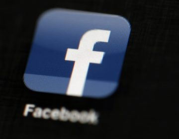 In this May 16, 2012, file photo, the Facebook logo is displayed on an iPad in Philadelphia. Facebook suspended Cambridge Analytica, a data-analysis firm that worked for President Donald Trump's 2016 campaign, over allegations that it held onto improperly obtained user data after telling Facebook it had deleted the information. (Matt Rourke/AP Photo, File)