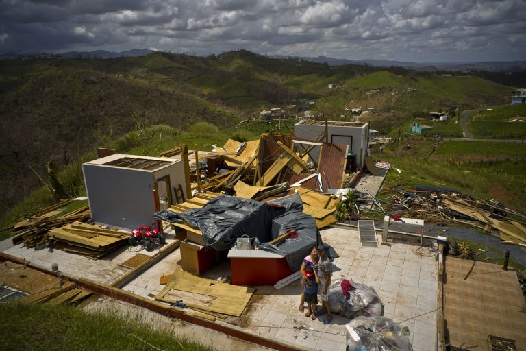A family stand next to their belongings, in front of the remains of their home destroyed by Hurricane Maria, in the San Lorenzo neighborhood of Morovis, Puerto Rico, Saturday, Oct. 7, 2017. (Ramon Espinosa/AP Photo)