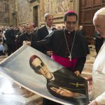 In 2015, Pope Francis is presented with an image of Roman Catholic Archbishop Oscar Romero during a private audience granted to participants to the pilgrimage from El Salvador at the Vatican. Pope Francis has cleared the way for slain Salvadoran Archbishop Oscar Romero to be made a saint, declaring that a churchman who stood up for the poorest of the poor in the face of right-wing oppression should be a model for Catholics today. (L'Osservatore Romano/Pool Photo via AP)