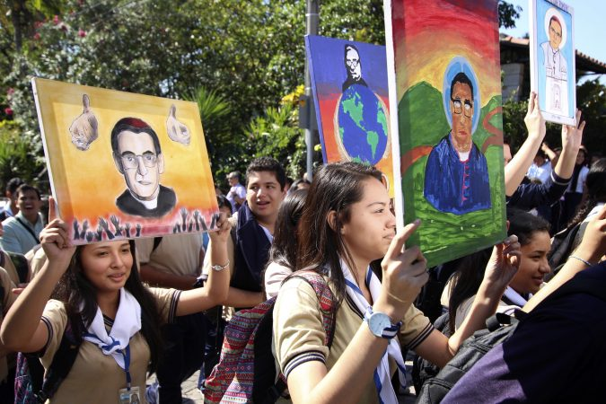 Students hold up art work depicting slain Salvadoran Archbishop Oscar Romero as they walk to the Divine Providence chapel, in San Salvador, El Salvador, Wednesday, March 7, 2018, where Romero was shot and killed as he celebrated Mass in 1980. Salvadorans are celebrating the news that Romero is to be made a saint. Pope Francis declared that the churchman who became a hero for standing up for the poor and oppressed should be canonized along with the reformer Pope Paul VI. (Salvador Melendez/AP Photo)
