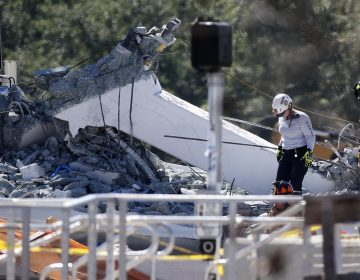 Rescue workers walk on the rubble after a brand-new pedestrian bridge collapsed at Florida International University in Miami on Thursday, March 15, 2018. The pedestrian bridge collapsed onto a highway crushing multiple vehicles and killing several people. (Wilfredo Lee/AP Photo)
