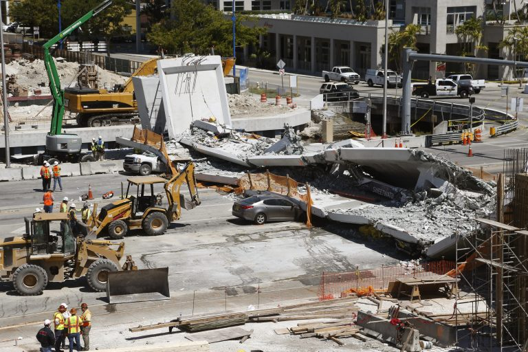 Crushed cars are shown under a section of a collapsed pedestrian bridge, Friday, March 16, 2018 near Florida International University in the Miami area. The new pedestrian bridge that was under construction collapsed onto a busy Miami highway Thursday afternoon, crushing vehicles beneath massive slabs of concrete and steel, killing and injuring several people, authorities said. (Wilfredo Lee/AP Photo)