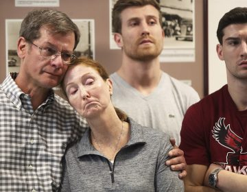 Parents John and Lisa Dombroski, left, stand with their sons John, behind, and Kevin during a press conference regarding their missing son and brother Mark, at the Hamilton Police Station in Hamilton, Bermuda, Monday, March 19, 2018. Mark Dombroski, 19, a member of the rugby team at Saint Joseph's University in Philadelphia, disappeared early Sunday after a night of socializing at the end of an international rugby tournament. (Blaire Simmons/The Royal Gazette via AP)