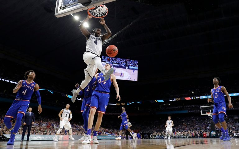 Villanova's Eric Paschall (4) dunks over Kansas's Mitch Lightfoot (44) during the second half in the semifinals of the Final Four NCAA college basketball tournament, Saturday, March 31, 2018, in San Antonio. (AP Photo/David J. Phillip)
