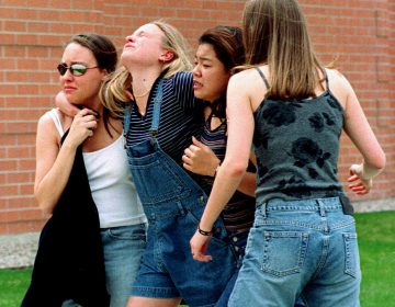 On April 20, 1999, unidentified young women head to a library near Columbine High School where students and faculty members were evacuated after two gunmen went on a shooting rampage in the school in the southwest Denver suburb of Littleton, Colorado.. Fifteen people, including the two shooters, died. (Kevin Higley/AP Photo)