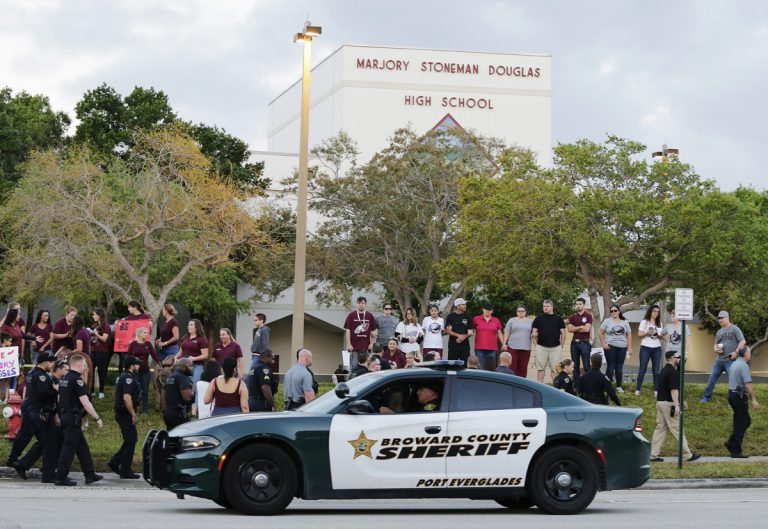 In this Feb. 28, 2018 photo, a police car drives by Marjory Stoneman Douglas High School in Parkland, Fla., as students returned to class for the first time since a former student opened fire there with an assault weapon.  (Terry Renna/AP Photo)