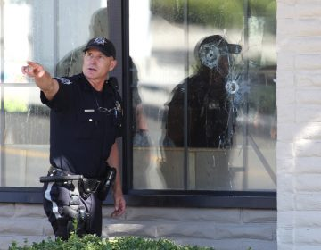 With bullet holes seen in a window, officers look for evidence at the scene of a shooting at an IHOP restaurant in Carson City, Nev. on Tuesday, Sept. 6, 2011. Seven people were wounded after a gunman opened fire at the restaurant, authorities said. (Cathleen Allison/AP Photo)