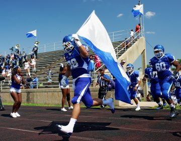 Senior Christian Sanchez caries the flag as the Cheyney University Wolves enter the O'Shields-Stevenson Stadium for the