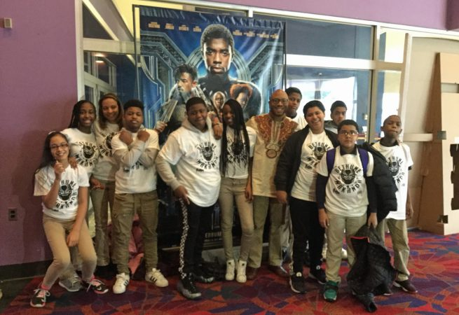 Seventh-grade English teacher, Herman Douglas, and his students pose in front of the Black Panther movie poster after seeing the movie. (Kyrie Greenberg/for WHYY)