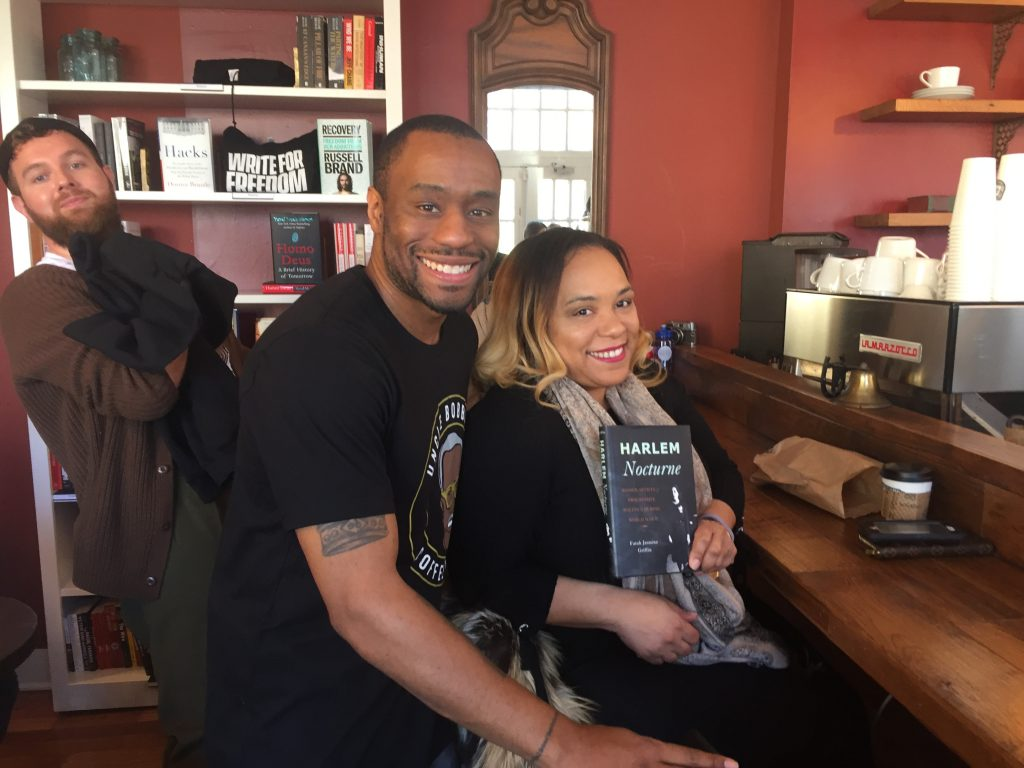 Marc Lamont Hill inside his coffeeshop with a patron.