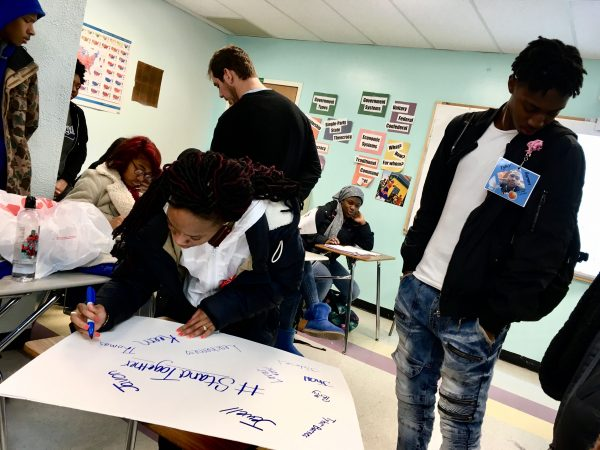 Freire Charter School students write the names of people they lost to gun violence on a poster.