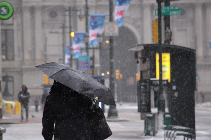 Umbrellas go up on Market Street near City Hall as the snow intensifies. (Emma Lee/WHYY)