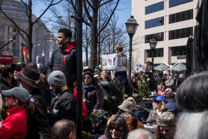 Demonstrators flood the streets of downtown Wahshington D.C. while others take a break at a restaurant during the March for Our Lives Saturday. (Brad Larrison for WHYY)