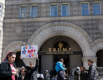 Demonstrators pass by the Trump International Hotel in downtown Washington D.C. Saturday afternoon during the March for Our Lives. (Brad Larrison for WHYY)
