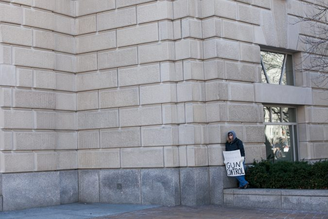 A lone protestor takes a break from the large during the March for Our Lives Saturday in Washington D.C. (Brad Larrison for WHYY)