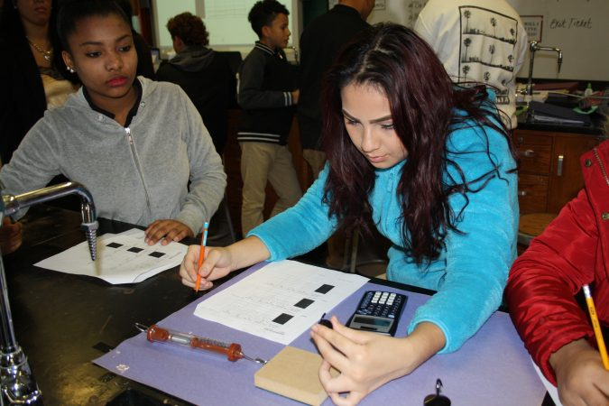 """Maria Ramirez, left, and Eunice Millán, both freshmen at Woodrow Wilson High School in Camden, New Jersey, are taking physics this year as part of a """"Physics First"""" initiative to prepare more students for STEM careers. (Tara García Mathewson/The Hechinger Report)"""