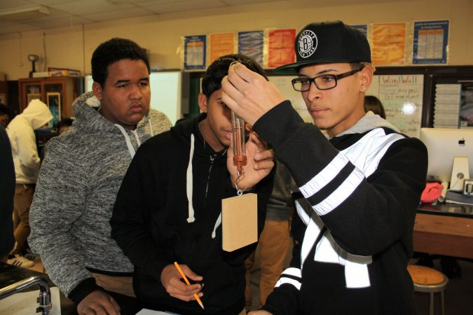 From left, Anderlis Martinez, Pedro Rosa and Jorge Suero are taking a Spanish-language physics course at Woodrow Wilson High School in Camden, New Jersey, as part of an effort to prepare more students for STEM careers. (Tara García Mathewson/The Hechinger Report)