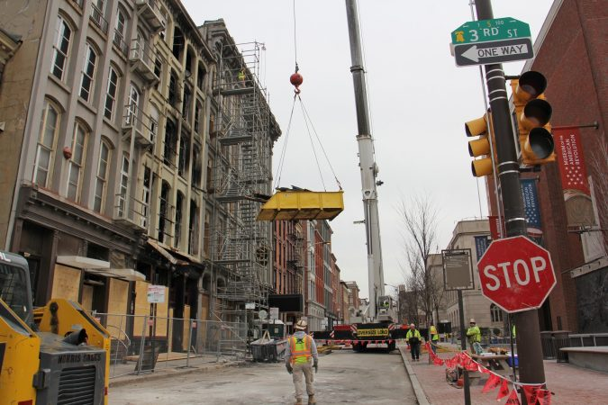 A crane lowers a load of debris from the roof of 239 Chestnut Street. (Emma Lee/WHYY)