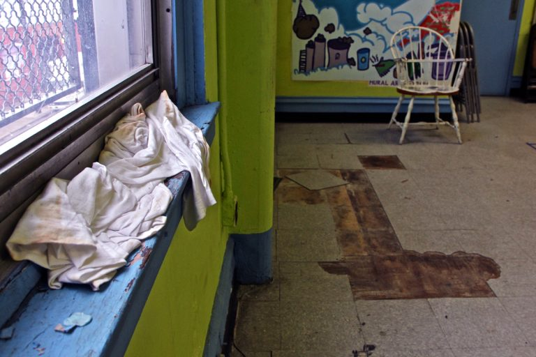 A T-shirt catches the drip from a leaking window frame in a multi-purpose room used by children at Vare Recreation Center in Grays Ferry. The 100-year-old building is badly in need of maintenance. (Emma Lee/WHYY)