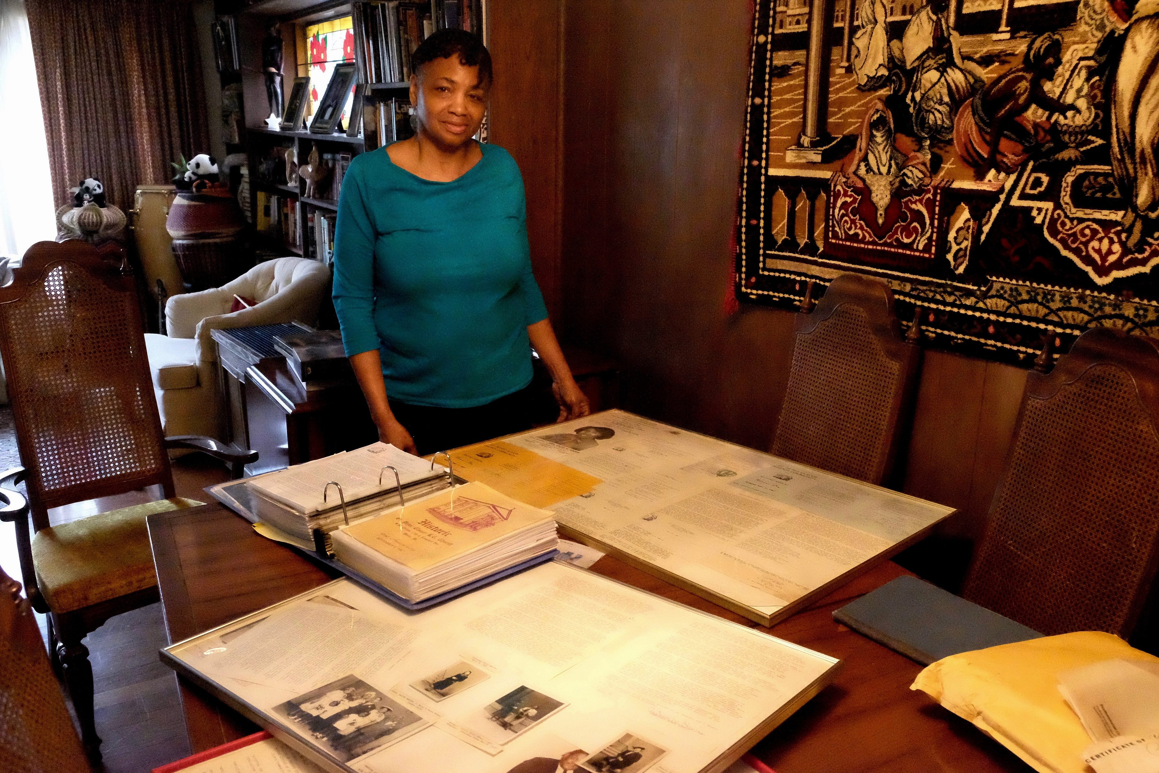 Adrienne Harris, a lifelong member of the St. Peter Claver Church and School community at home with some of her collected parish history.