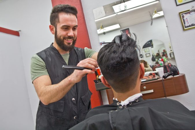 Alberto Carrasco is the owner of D'Classico Barbershop in Olney. (Kimberly Paynter/WHYY)