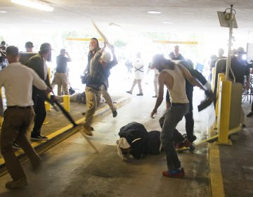 DeAndre Harris, seen balled on the ground, suffers a beating in a parking garage near the Charlottesville police station after the white nationalist rally last August. Zach D. Roberts/AP