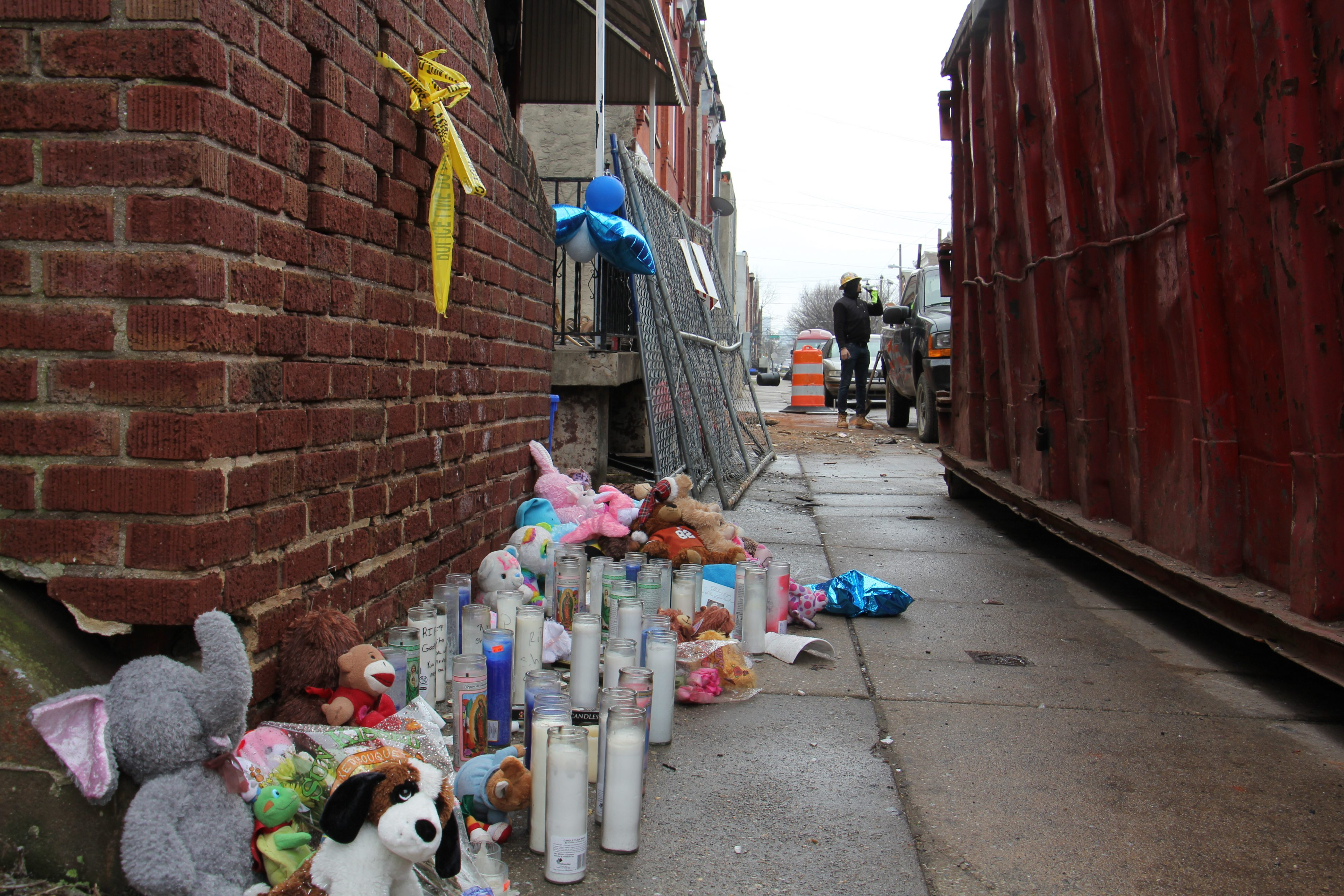 Balloons, candles and plush toys memorialize the four people killed in the house fire.