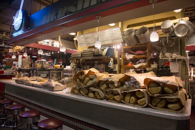 70 loaves of bread join the oven fresh meats on the counter of Hershel's as the morning prep continues. (Emily Cohen for WHYY)