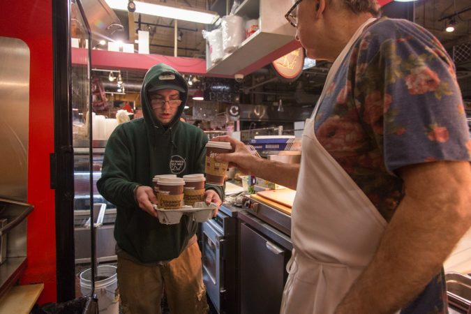 Russell Grasso, 23, arrives at 6am with some much needed coffees in hand for each of the deli workers. (Emily Cohen for WHYY)