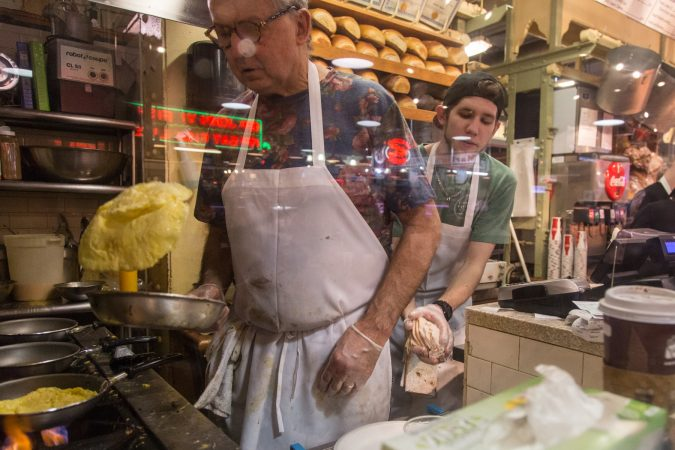 Head chef, Andy Wash, prepares some omelets as Ian McClendon, 23, sneaks in behind to refresh his cheese supply. (Emily Cohen for WHYY)