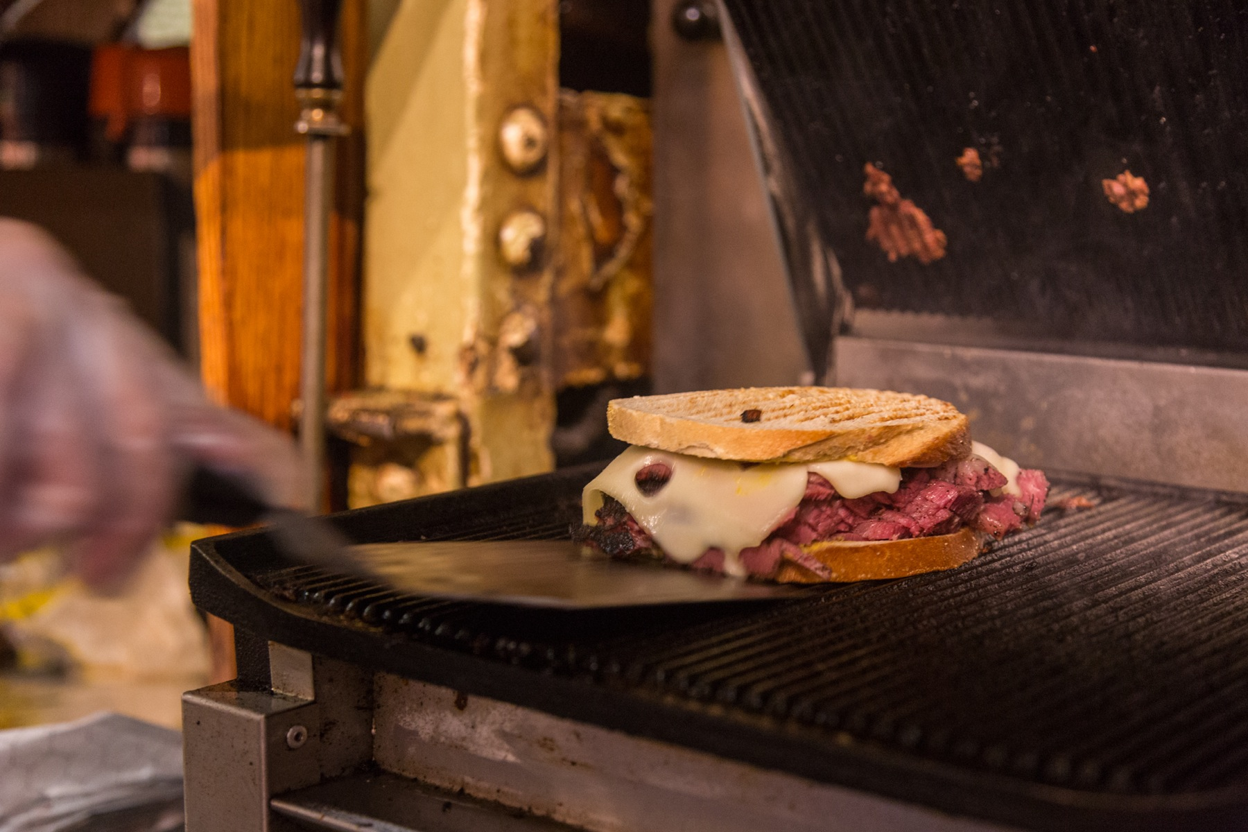 A grilled Pastrami special is taken from the grill.