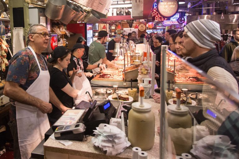 Hershel's East Side Deli chef and co-owner Andy Wash (left) and his crew tend to customers. With a seemingly endless line, it is all hands on deck with each worker prepping different orders.