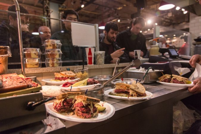 Patrons line up to pay as their sandwiches are readied. (Emily Cohen for WHYY)